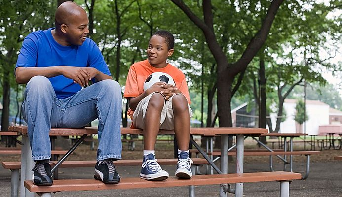 Adult and youth holding a soccer ball sitting on a bench.