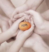 "Image of hands holding a stone with ""HOPE"" written on it"